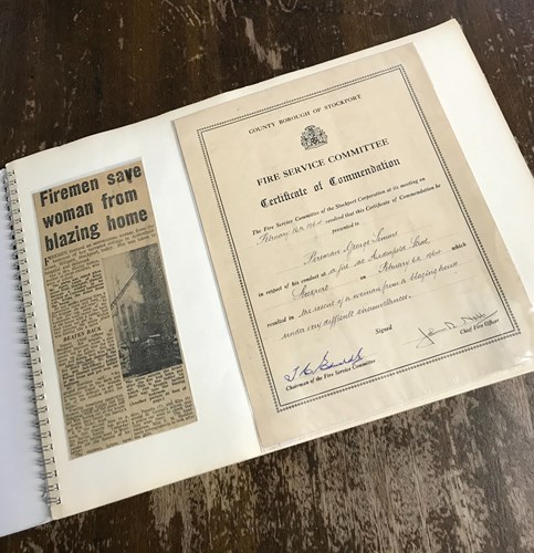 George's certificate of commendation awarded during his time as a firefighter and newspaper extract titled 'firemen save woman from blazing home'