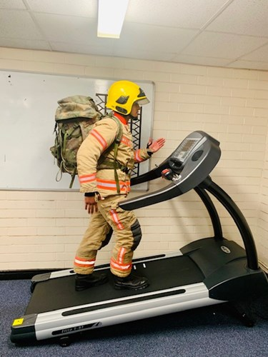 A firefighter on a treadmill wearing a backpack